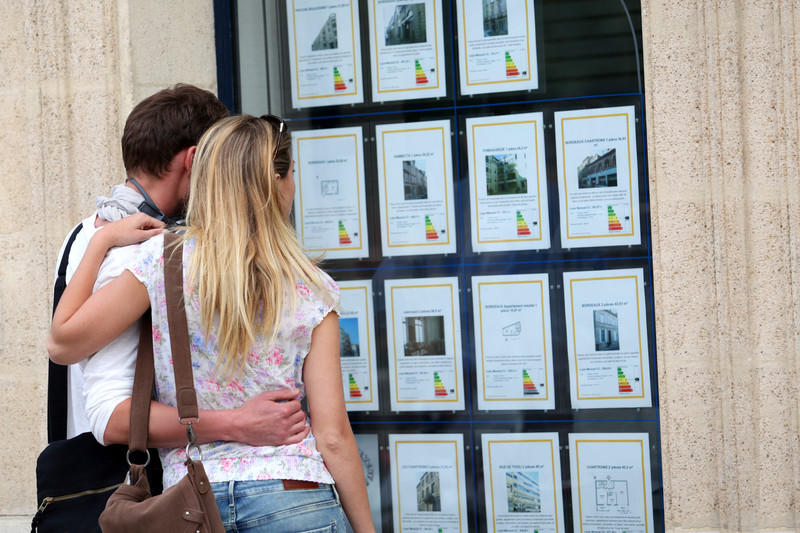 couple looking at properties in estate agents window